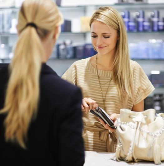 blonde girl paying for cosmetics