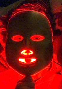Editor using a light therapy mask on the red light setting
