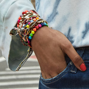 Woman wearing a stack of charm bracelets including a puka shell bracelet