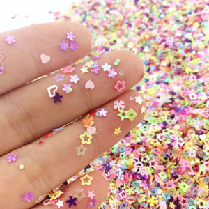 Hand holding multicolor nail glitter confetti in a variety of shapes and colors