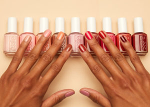Woman's hand fanned out over a variety of Essie nail polishes