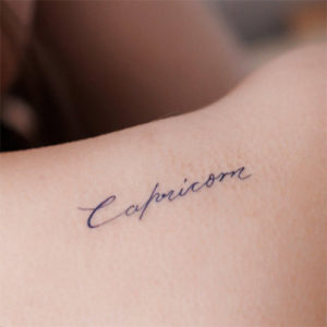 Back shoulder temporary tattoo that says 'Capricorn' in cursive