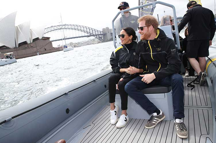 Meghan Markle wearing black and white Veja leather sneakers with Prince Harry at 2018 Invictus Games