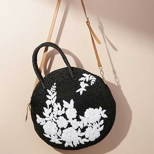black circle straw bag with leather strap and white embroidered flowers