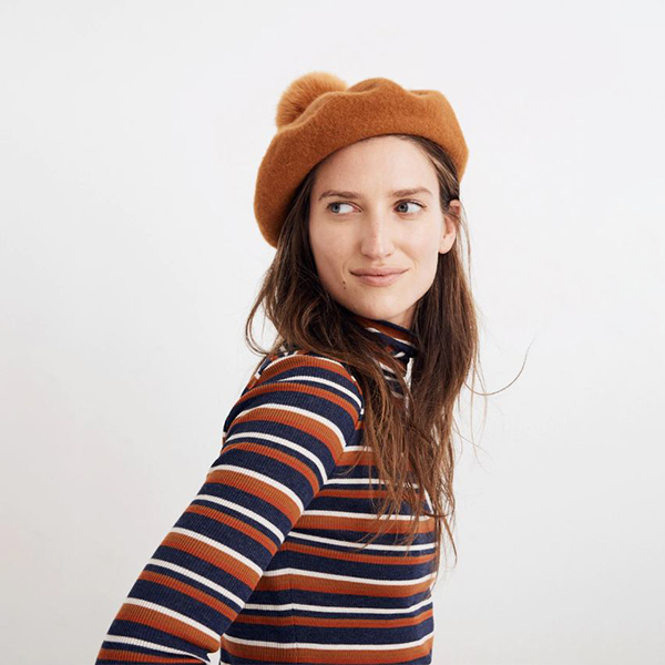 Model wearing tan beret with pom-pom