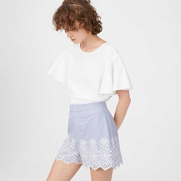 Model wearing white blouse with blue, structured, eyelet lace shorts.
