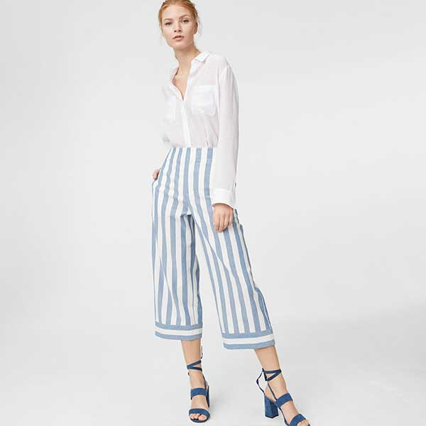 Model wearing white button-up, blue and white striped pants, and heels.