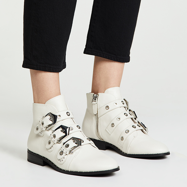 Model wearing white western inspired ankle booties with silver buckles