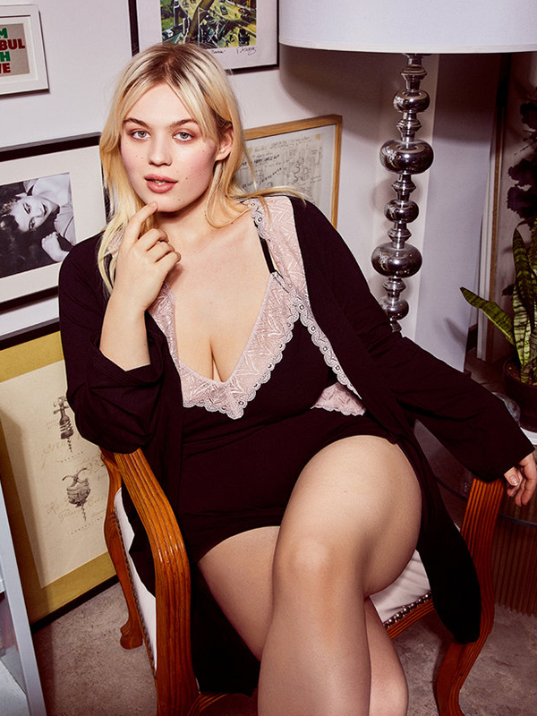 Model wearing a matching black tank top, shorts, and robe with pink lace trim from Cosabella x Eloquii's plus size lingerie collab