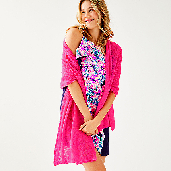 Model wearing a floral printed dress with a pink cashmere wrap