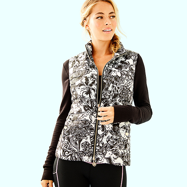 Model wearing a black long sleeve shirt and a black and white printed puffer vest