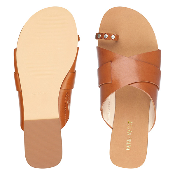 Tan flat sandals with toe strap.