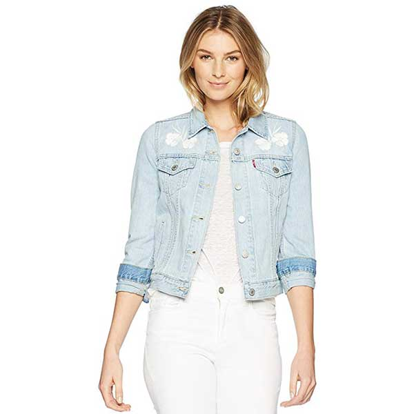 Model wearing light denim jacket with white floral embroidery.
