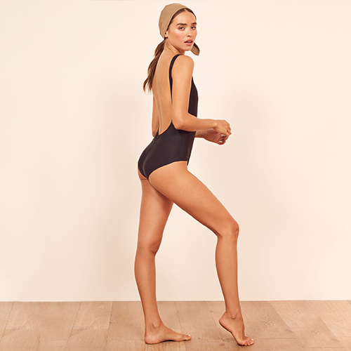 Woman modeling a black one piece, low back Reformation swimsuit