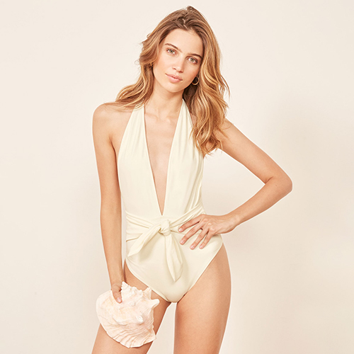 Woman modeling a plunging ivory one piece Reformation swimsuit