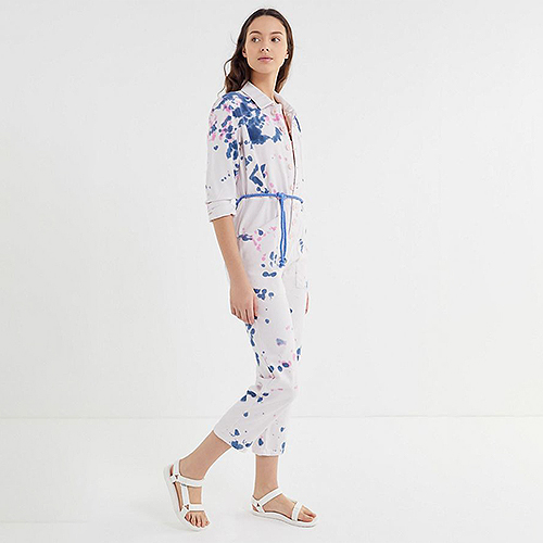 Woman wearing a white jumpsuit with blue and pink splatters