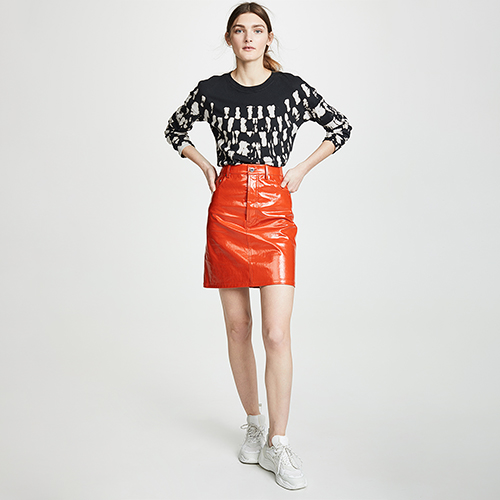 Woman wearing a black and white long-sleeve tie-dye shirt with an orange skirt